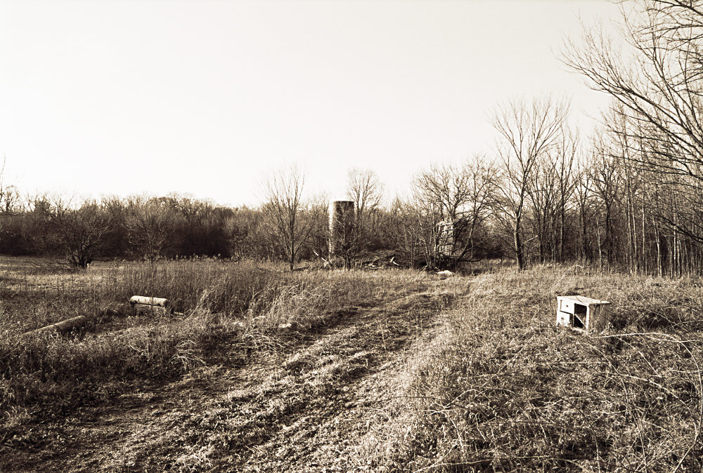 An abandoned plot of land with a fallen home and derelict silo in the distance, rendered in monochrome. Belongings are strewn about some tire-flattened grass.