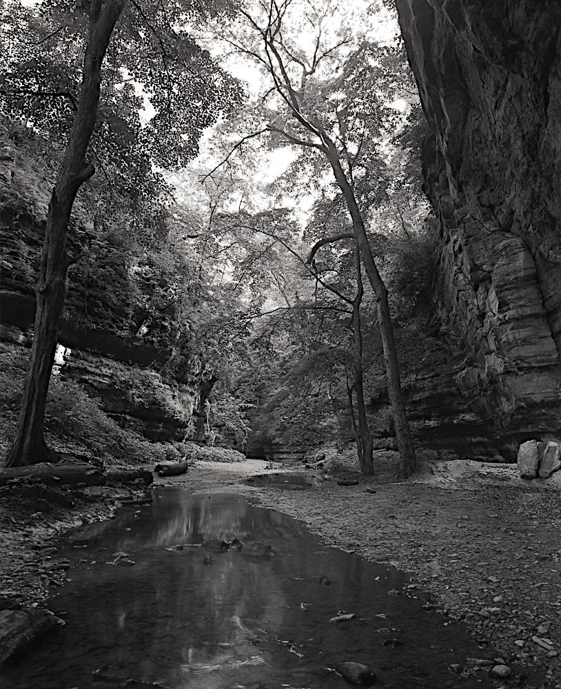 A dramatic monochrome of a stream running between two large bluffs.